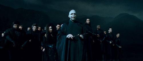 Lord Voldemort en premier plan en tenant sa baguette avec les Mangemorts derrière