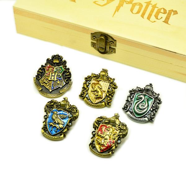 Médaillons / pins des 4 maisons de poudlard avec boîte Harry Potter sur fond blanc