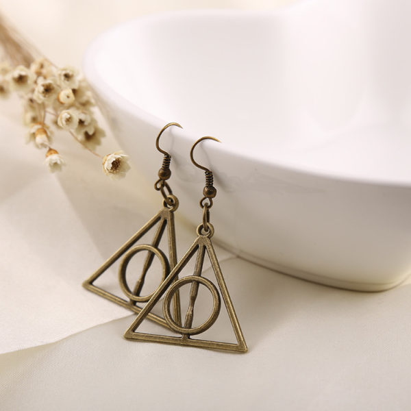 deux boucles d'oreilles harry potter avec le logo reliques de la mort couleur or accrochés sur un fond blanc